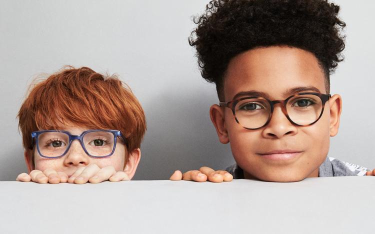 two boys peeking heads above tabletop